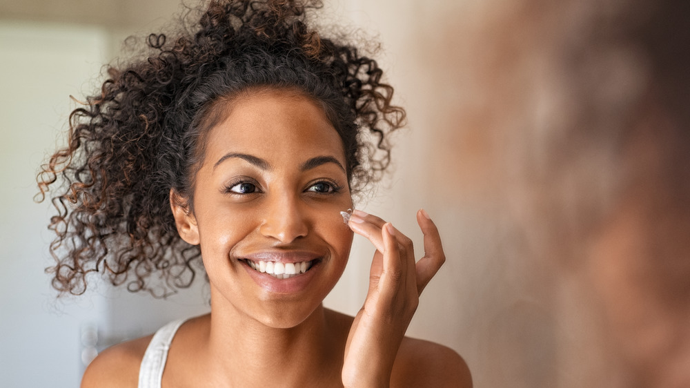 A smiling woman applying lotion to her face