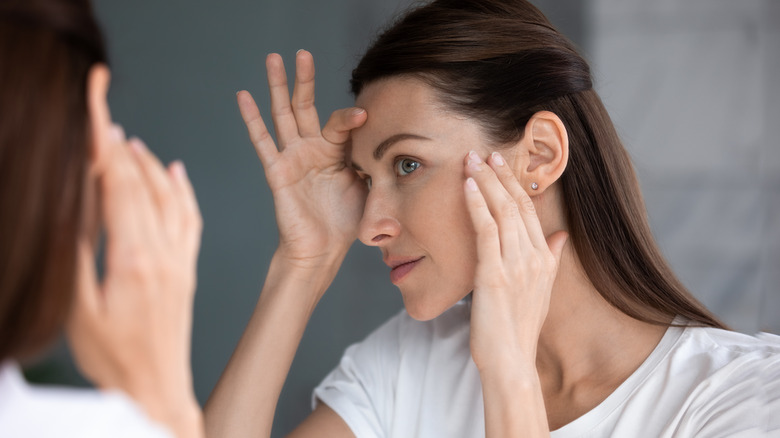 Woman looking in a mirror inspecting her skin