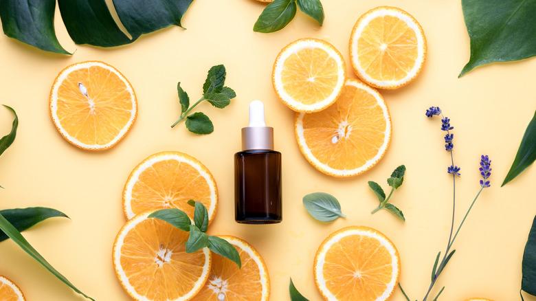 Vitamin C serum with sliced orange and herbs