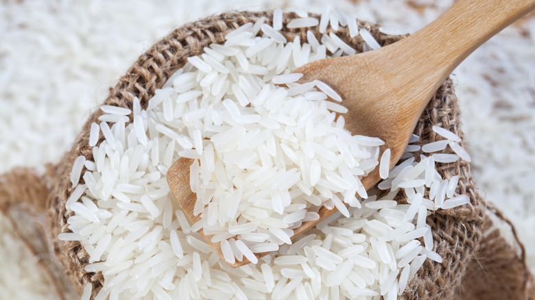 Wooden spoon of raw rice