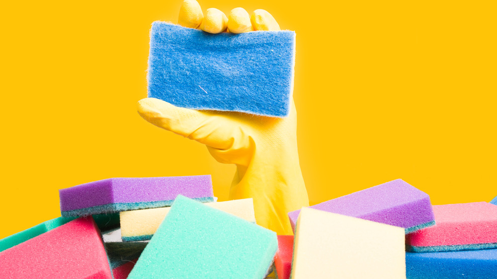 Yellow gloved hand holding a blue sponge amid a pile of colorful sponges