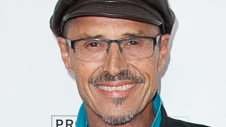 Soap star Michael Nader poses with a smile wearing glasses and a leather hat.