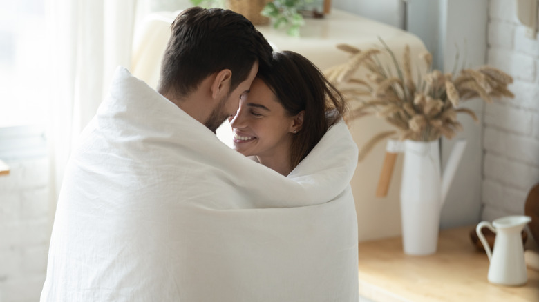 Couple cuddled up together in a white blanket