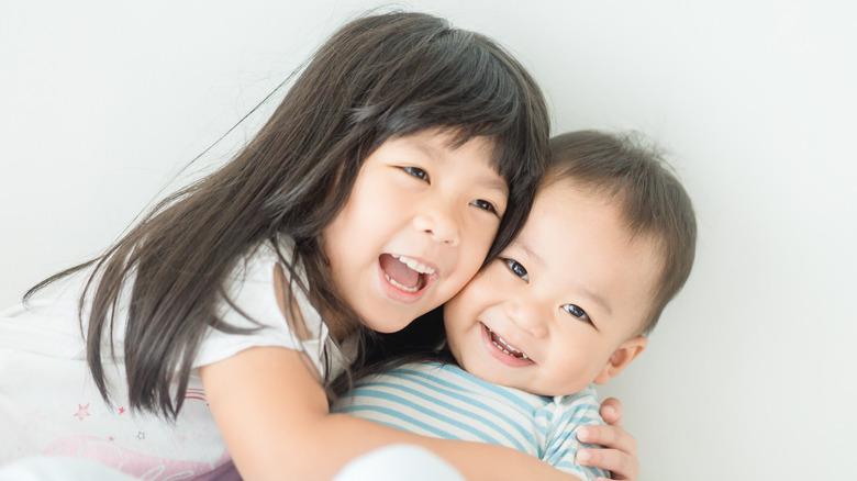 Baby girl hugging sibling