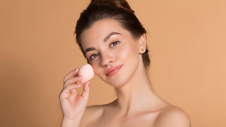 Woman applying makeup with a beauty blender sponge