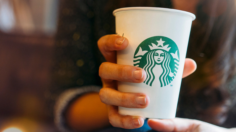 hand holding a tall Starbucks drink