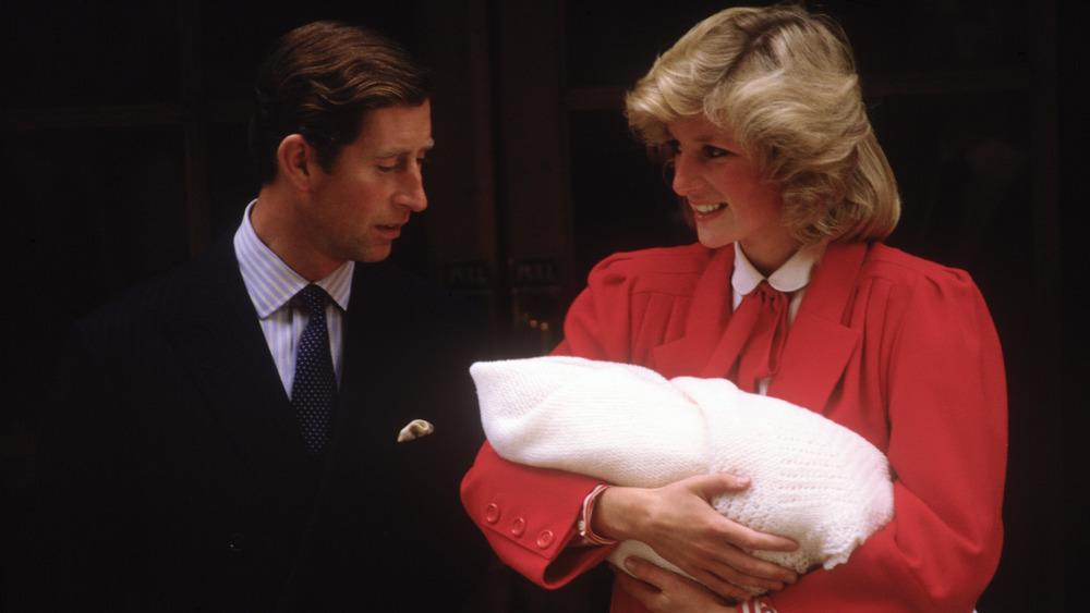 Princess Diana cradling Prince Harry with Prince Charles