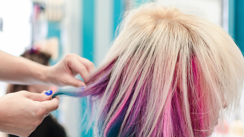 Woman with multi-colored hair and a cowlick gets it style by another woman.