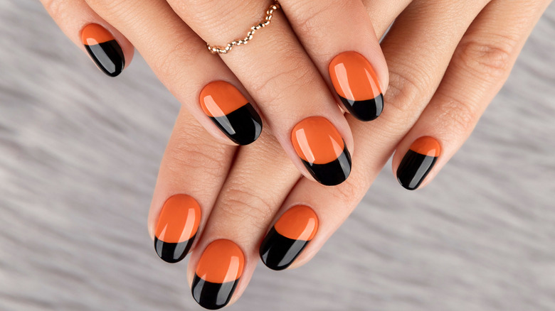 Orange and black-painted nails