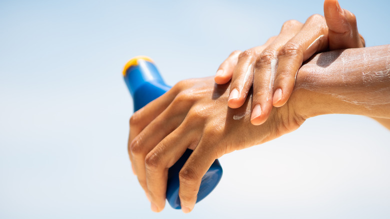 Woman applying sunscreen to her hands
