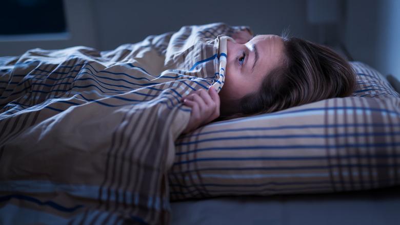 Frightened person hiding under blanket