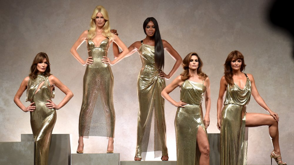 Five supermodels posing in gold gowns