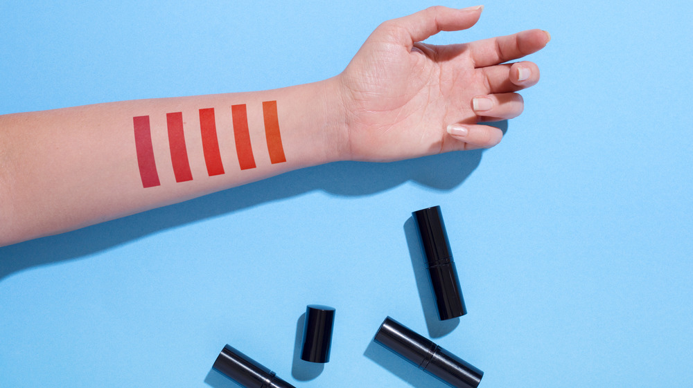 Red lipstick swatches on forearm