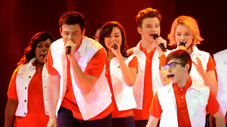 The cast of Glee singing into microphones
