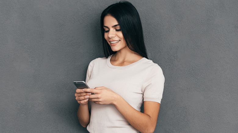 woman smiling and texting