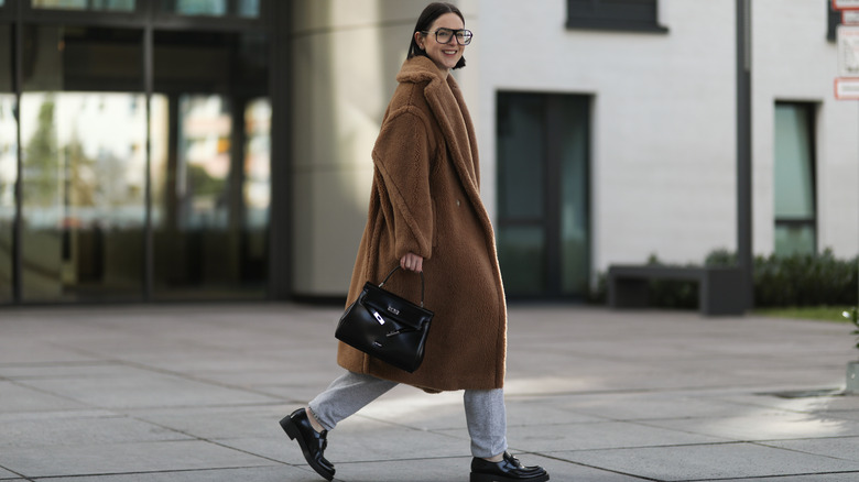 Woman walking with oversized coat and gray sweatpants