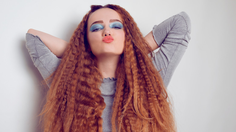 Girl with red hair and blue eyeshadow wearing voluminous, crimped hairstyle