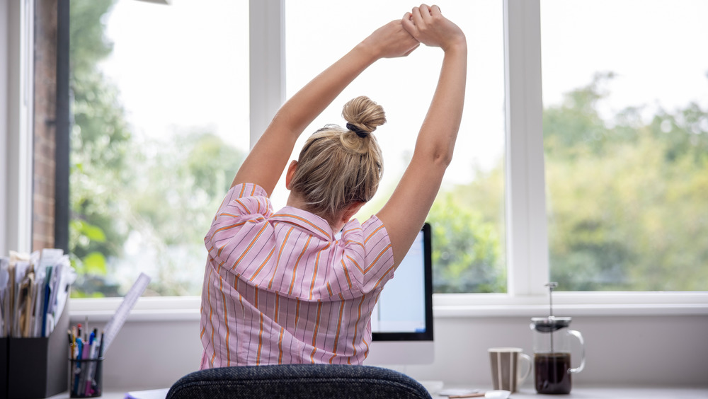 A woman stretching in front of a computer