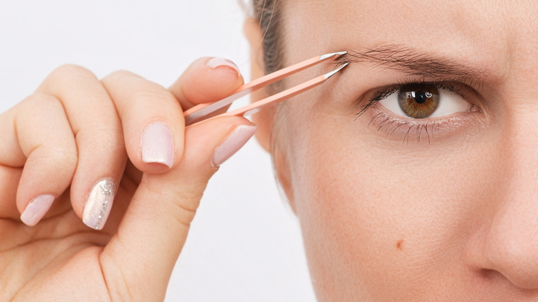 Unhappy woman plucking her eyebrows
