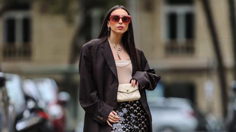 Gabriella Berdugo wears an oversized blazer, a Chanel quilted belt bag, a crop top, a sequin skirt, and Nike Air sneakers in Paris, France