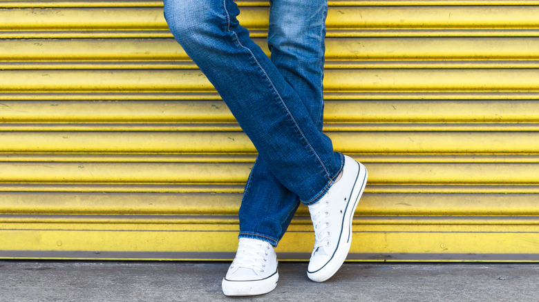 Woman wearing jeans and sneakers posing against a garage door.