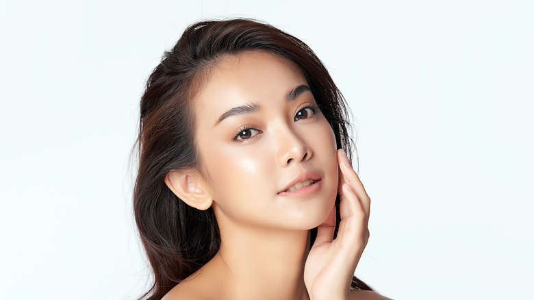 woman with good skin touching face