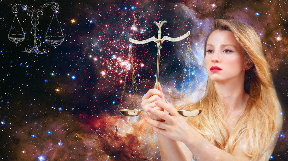 Woman holding Libra scales in starry sky
