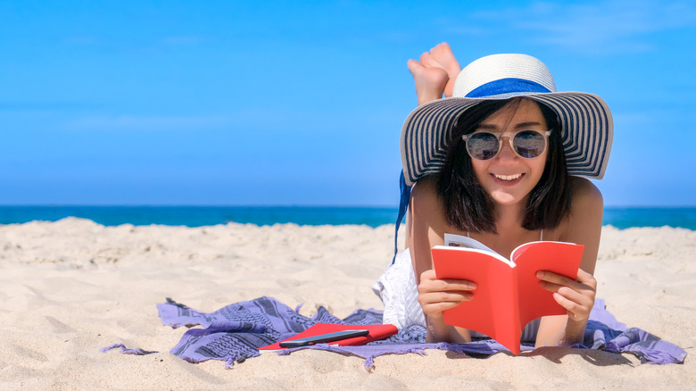 woman reading happily on beach