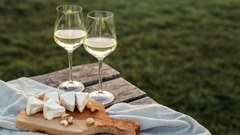 Glasses of wine next to a platter of cheese