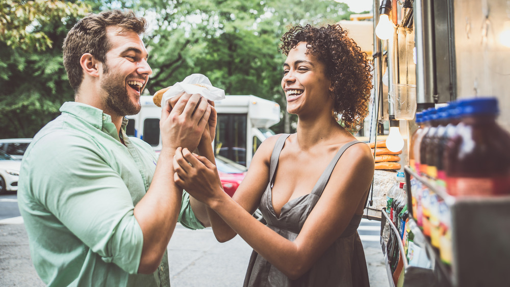 Millennial couple eating hot dogs from food cart
