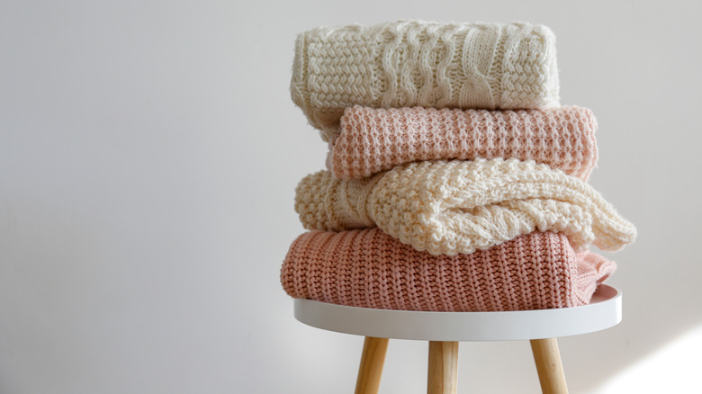 Pastel sweaters stacked on table