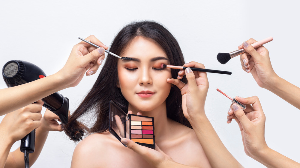 Multiple hands doing makeup, hair on woman