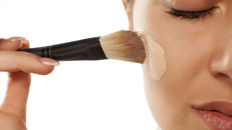 woman applying foundation with eyes closed
