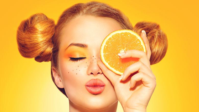 Woman with orange lipstick holding orange slice to her eye