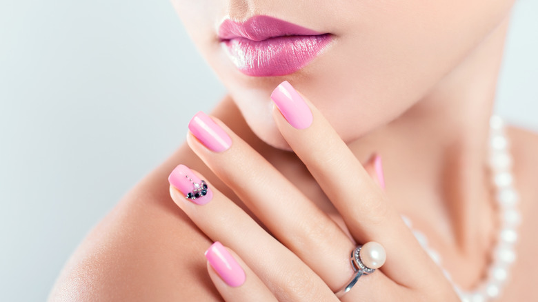 model posing pink nails while wearing pink lipstick and pearls