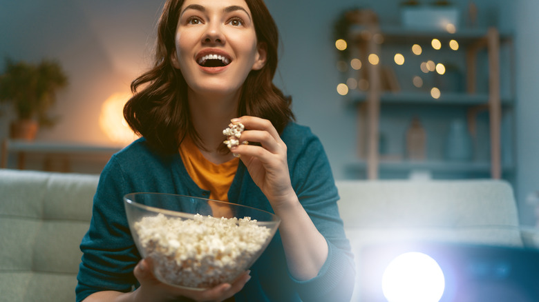 Woman eating popcorn while watching a feel-good film