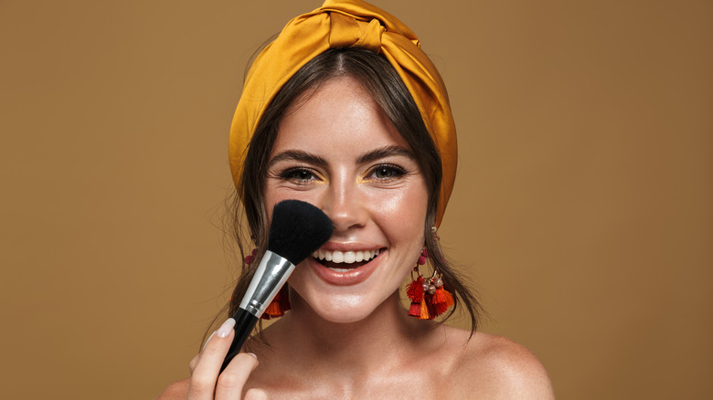 A woman applying foundation with a brush