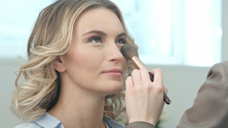 Makeup artist applying makeup under woman's eyes