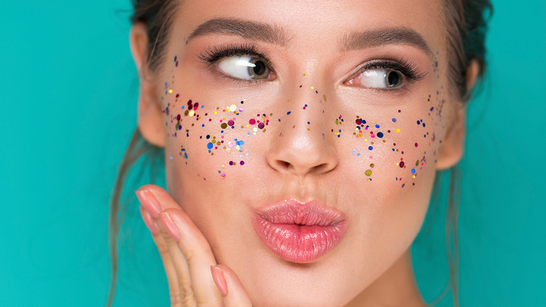 Woman with glitter lip gloss and glitter on face