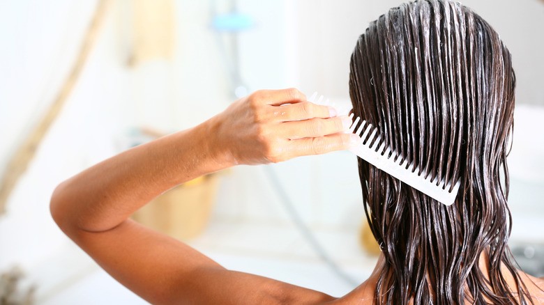 Woman brown hair applies conditioner to hair with comb