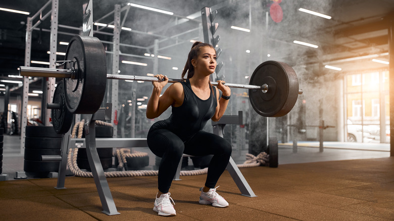 powerlifter squatting in fitness studio gym and using heavy barbell for a squat