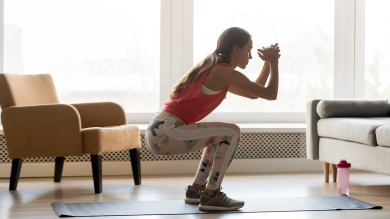 young white woman in coral top and leggings performing a squat in her living room