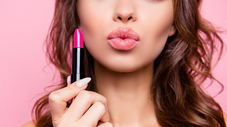 Woman holding up a pink lipstick