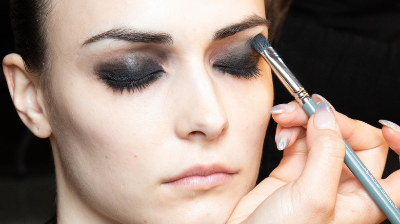 Model getting smokey eyeshadow applied