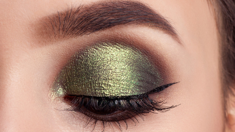 Close-up of woman with olive green eyeshadow look
