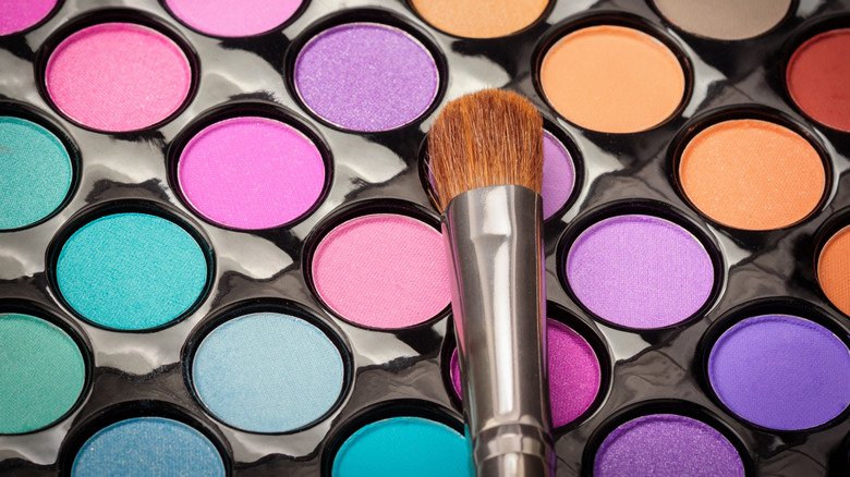 An eyeshadow palette and brush