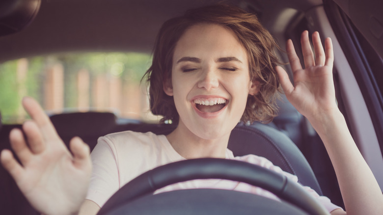 Woman driving and listening to entertaining media