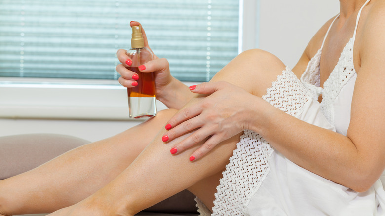 Woman applying tanning lotion