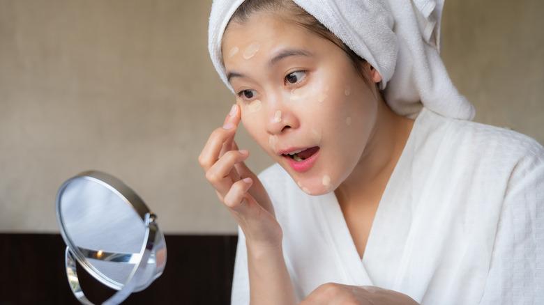 Woman applying lightweight foundation on skin