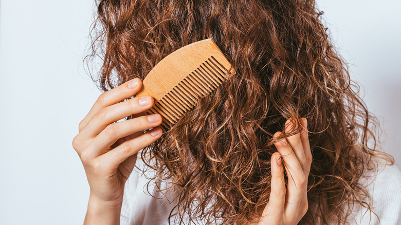 Woman combing her curly hair